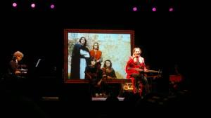 """Red Canzian durante lo spettacolo, con alle spalle la foto dei Pooh ai tempi dell'album """"Parsifal"""", 1973"""